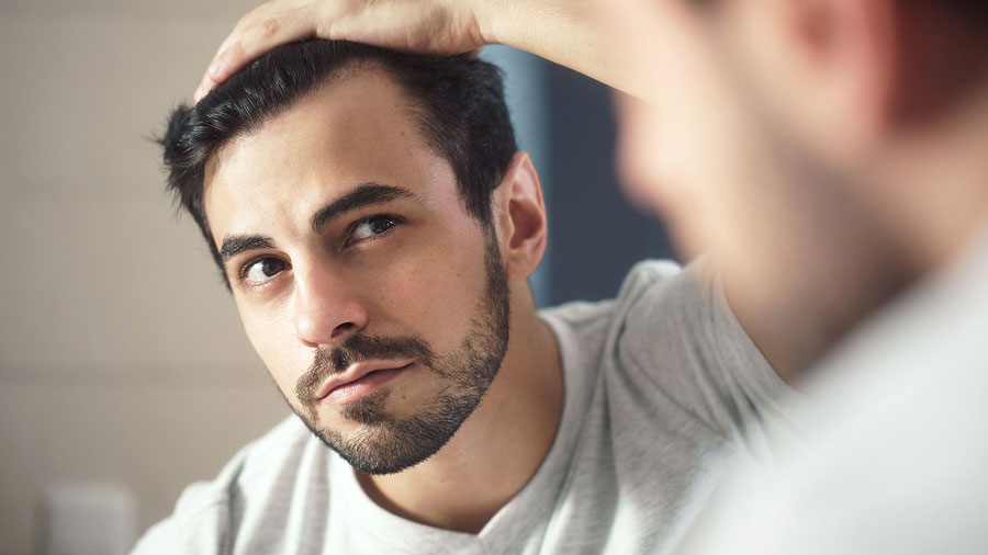 A man looking at his hair loss in the mirror